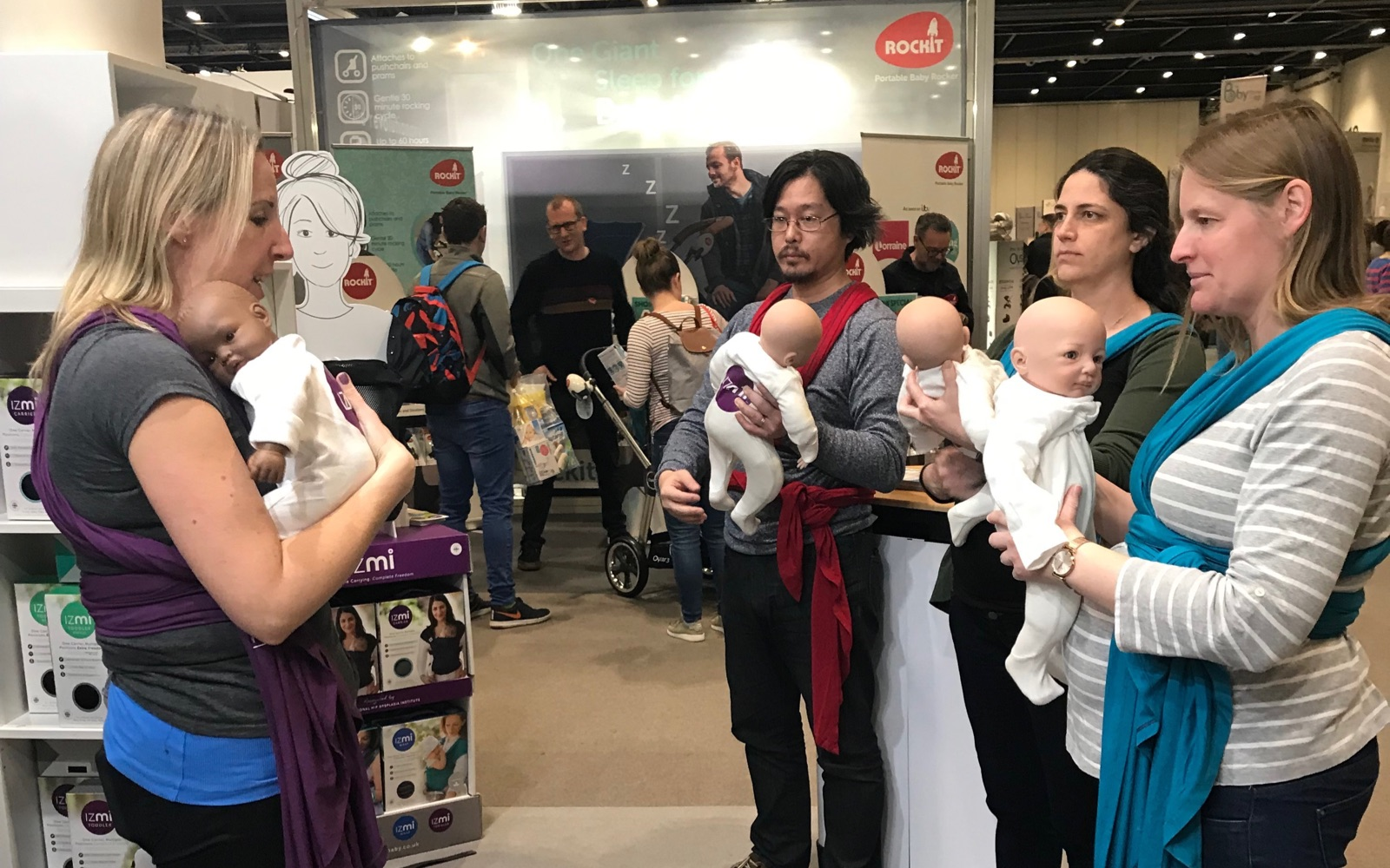 Roamy demonstrating how to use a babycarrier to a small group of people